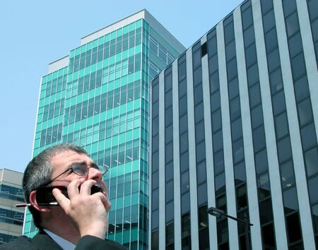 technology deal: A businessman speaking to the phone in a big city. soft focus on the man head.