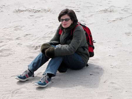 A girl sitting in the sand on the ocean beach in a very cold and windy winter day           Stock Photo