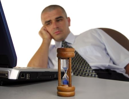 A tired businessman in the end of the workday at the desk-metaphor....:)..The focus is on the sandglass and foreground,the man is blurred           photo