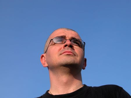 resolute:  Bald man head with glasses looking away over the blue sky