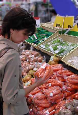 Woman shoping in a supermarket in the vegetables area           photo