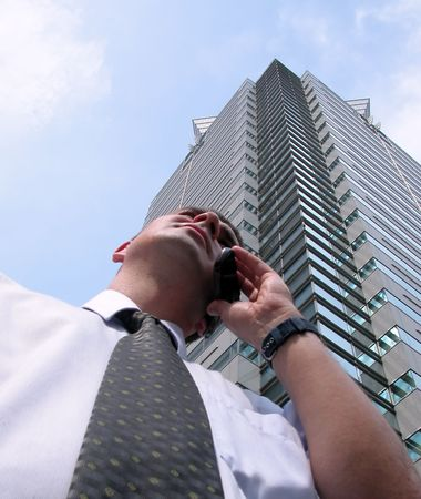 Businessman using obile phone in a big city.Soft focus on the man.           photo