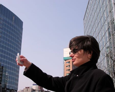 Businesswoman taking images with a cellular phone photocamera in a big city.          photo