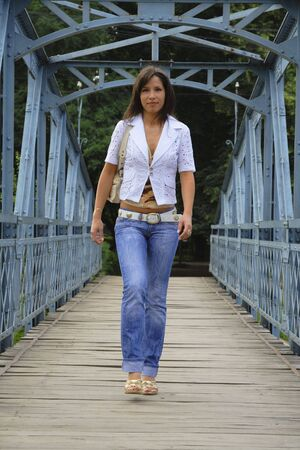 Young woman walking on a old bridge. Stock Photo - 1201980