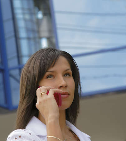 Portrait of a businesswoman using a mobile phone in front of a corporate building. Stock Photo - 1201983