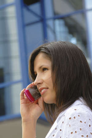 Portrait of a businesswoman using a mobile phone in front of a corporate building. Stock Photo - 1201984