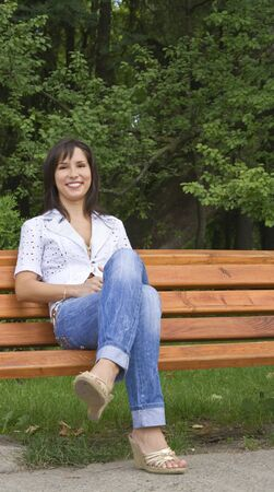 gril: Portrait of a smilling young woman sitting on a bench in a park. Stock Photo