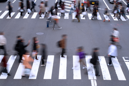 woman street: Motion blur aspect of people crossing the street in a big city.