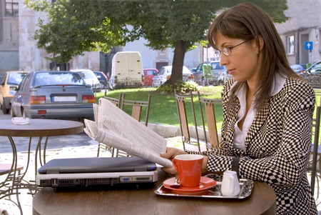 Young businesswoman at a coffee terrace reading the newspaper. Stock Photo - 1585484
