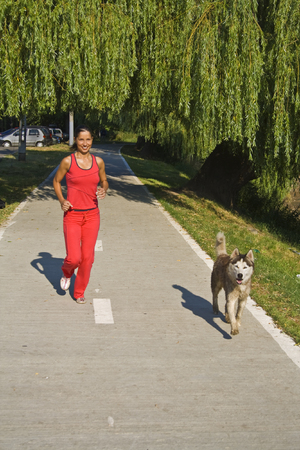 Young woman and her dog running in the morning.  photo