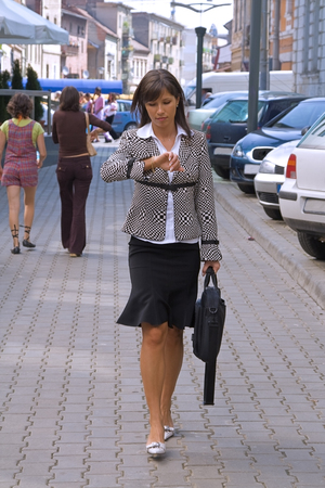 Walking businesswoman while she is cheking the time Stock Photo - 1622489