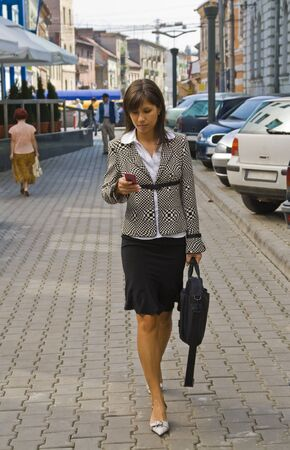 phone the clock: Businesswoman checking her mobile while she is walking. Stock Photo