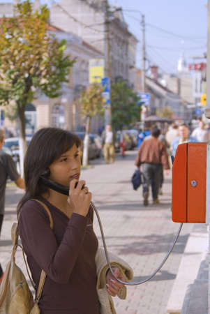 Image of a young woman at the public phone in a city street. photo
