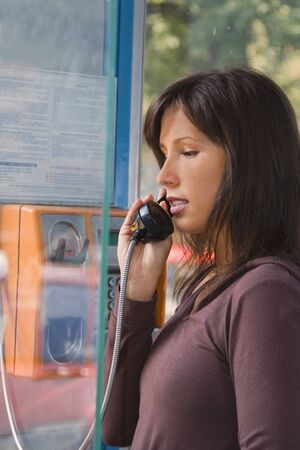 Beautiful teen brunette using a public phone in a cabin.The left part of the image has a special lighting provided by reflectionrefraction through a glass open cabin door. photo