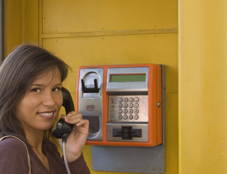 analogue: Image of a beautiful young smiling woman in a public phone cabin.