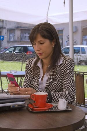 Young businesswoman checking her mobile phone agenda while she is enjoying a morning coffee break on an urban terrace. Stock Photo - 1796171