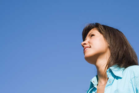 Profile of a smilling brunette with an optimistic attitude over a blue sky. Stock Photo - 1796160