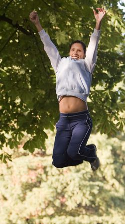 gril: Girl jumping in a park over the trees background.