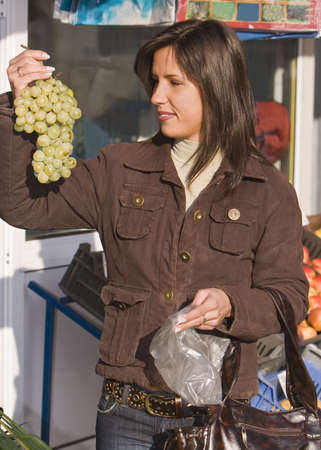 Image of a young woman in a vegetable market buying grapes. Stock Photo - 1945153