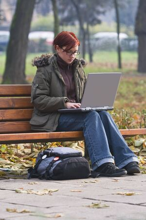 Redhead girl working on a latop in an autumn park photo