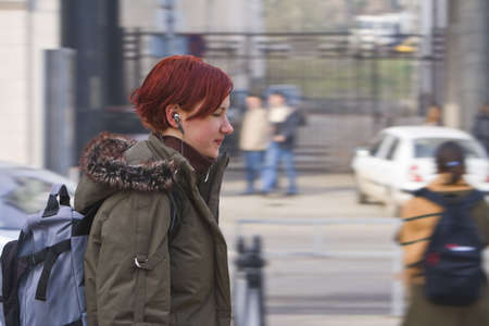 Redhead girl listening to music while walking in a city photo