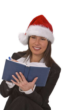 desired: Young woman with Santas hat taking notes about the desired Christmas gifts.  Stock Photo
