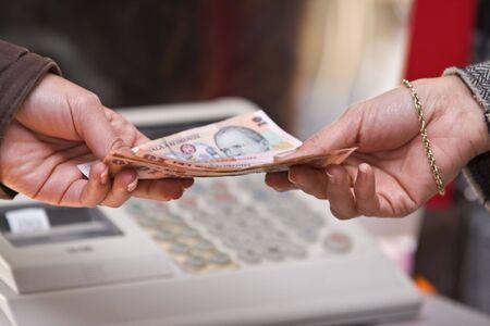 Detalle de la mano de una mujer mientras ella está pagando en la tienda (rumano dinero).  Foto de archivo