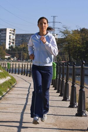 Young woman jogging in the morning on the riverside in a city.