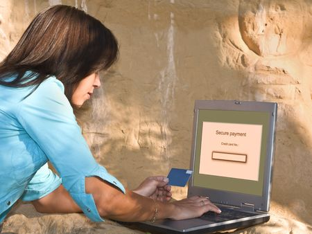 secured payment: Young woman doing an online credit card payment in a rocky environment. Stock Photo