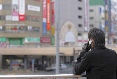 adds: Business using mobile phone in a big Japanese City.Extreme selective focus on the phone and mans head.The buildings and the adds are completelly out of focus but preserve the Asian city atmosphere in the image.