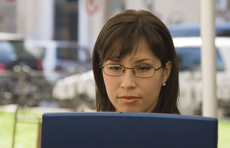 Image of a businesswoman working on a laptop at a terrace in a big city. photo