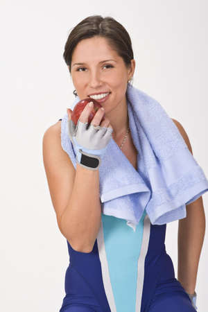 Relaxed young woman in fitness equipment holding an apple.Ideal image to illustrate the concept of healthy lifestyle (sport and correct nutrition). Stock Photo - 2388884