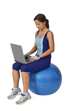 Woman in fitness equipment sitting on a gym ball and working on a laptop.Conceptual image to show the universality and mobility of technology and information. photo