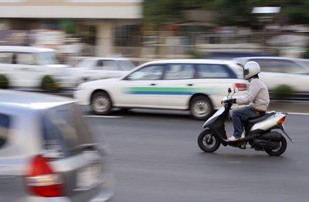 vespa: Panning imagen de una scutter en el tr�fico en una ciudad por carretera.