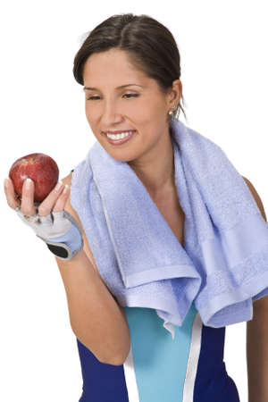 Relaxed young woman in fitness equipment holding an apple.Ideal image to illustrate the concept of healthy lifestyle (sport and correct nutrition). Stock Photo - 2441952