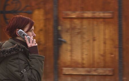 panning: Panning image of a redheaded girl using a mobile phone against a background consisting of a wooden traditional door.