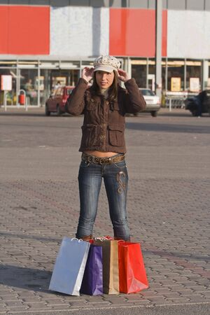 Image of a girl with many shopping bags fitting her hat in front of a mega-store. Stock Photo - 2544129