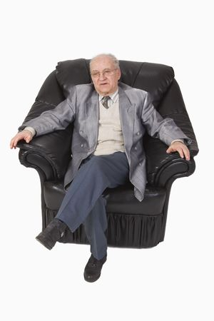 expertize: Image of a senior speaking while he is sitting relaxed in an armchair-upper view.