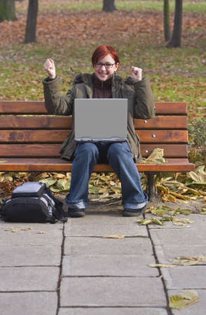 Happy redheaded girl with a laptop in an autumn park. photo