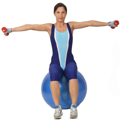 Woman doing bar-bells exercise while is sitting on a gym ball. Stock Photo - 2639850