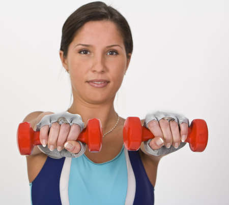 Image of a young woman doing barbells exercises,selective focus on the barbells. Stock Photo - 2655218