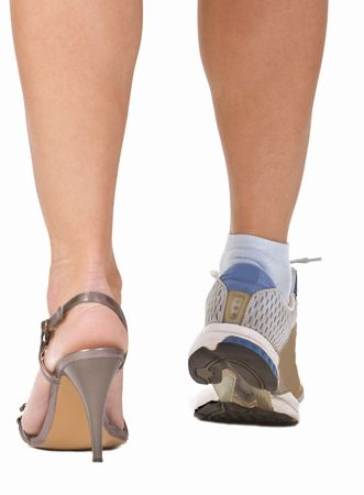 Image of a womans legs as she is wearing a highheel sandal and a sports shoe. Conceptual abstract image which emphasizes the importance of sport. Stock Photo