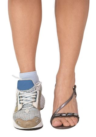 importance: Image of a womans legs as she is wearing a highheel sandal and a sports shoe. Conceptual abstract image which emphasizes the importance of sport. Stock Photo