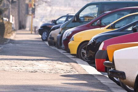 kerb: Row of different cars parked in a crowded city. Stock Photo