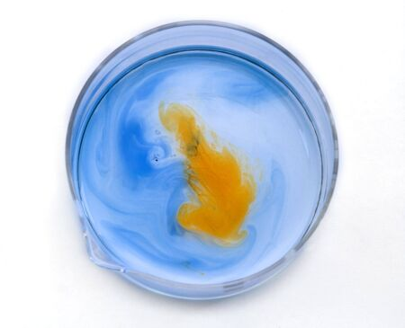 dissolution: Blue and orange substances dissolving and blending in a glass recipient-upper view.