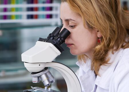 Female researcher looking through a microscope in a laboratory. photo