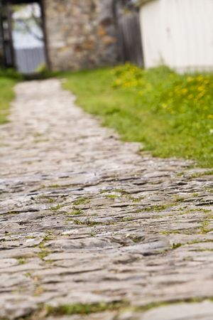 stone of destiny: Shot of a cobbled footpath ending at an open door. Interesting perspective and extremely selective artistic focus somewhere on the path. The rest is blurred enhancing the general idea of this image: destiny... Stock Photo
