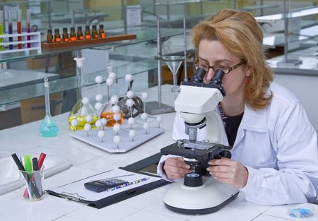 Female researcher looking through microscope in a laboratory. photo