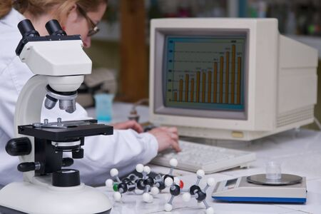 A female researcher analyzing some data at her lab desk.The image on the computer screen is mine.Selective focus on the microscope. Stock Photo - 3077680