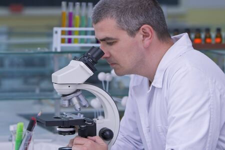 Male researcher looking through a microscope in a laboratory. photo